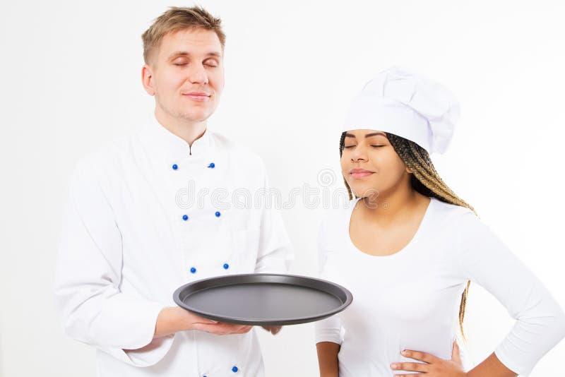 Een team van chef-koks snuift het prettige aroma van iets op een leeg die dienblad op wit wordt geïsoleerd stock fotografie