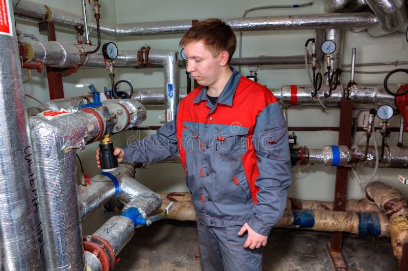 Een Technicus het inspecteren verwarmingssysteem in ketelruim stock afbeelding