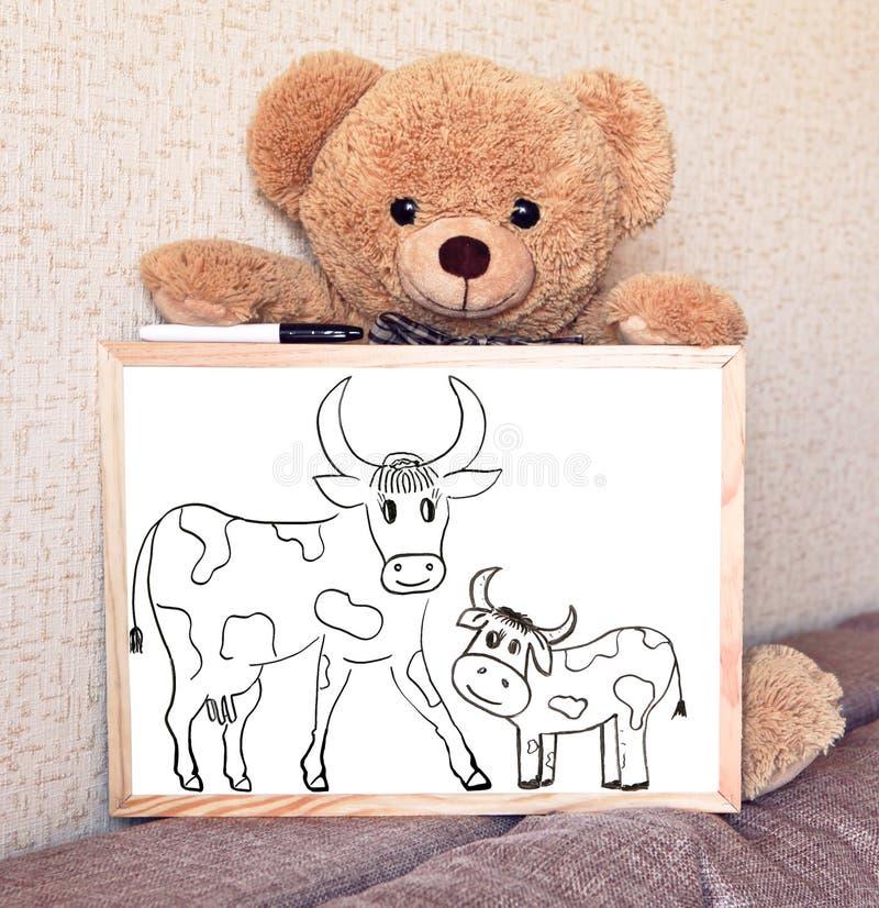 Een Teddybeerstuk speelgoed houdt een Tekenbord met een koepatroon met een kalf royalty-vrije stock fotografie