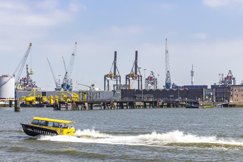 Een tedere boot van SS Rotterdam met op de achtergrond de kranen in Waalhaven van Rotterdam vervoerden heen en weer passagiers royalty-vrije stock foto
