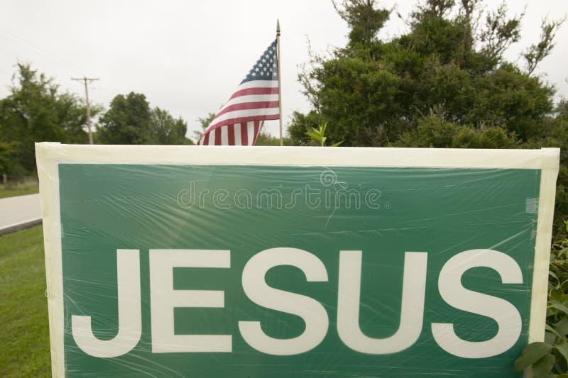 Een teken leest Jesus die het Christelijke standpunt naast een Amerikaanse Vlag bevorderen, die de scheiding van Kerk en Sta vert stock fotografie