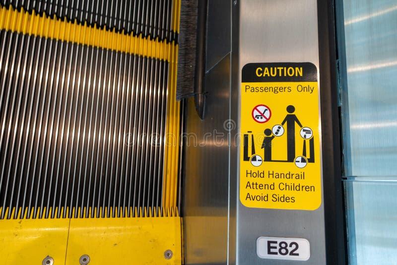 Een teken op de mensen van een escaltorwaarschuwing om voorzichtigheid te nemen stock foto