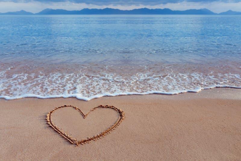 Een tekening van een hart als liefdesymbool op een geel zand op zee royalty-vrije stock fotografie