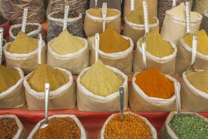 Een teller met plastic zakken van diverse gekleurde Indische kruiden en lepels royalty-vrije stock foto's