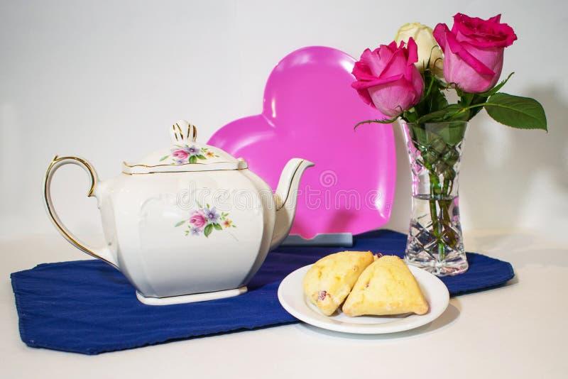 Een theepot, een roze hart, rozen en scones stock foto