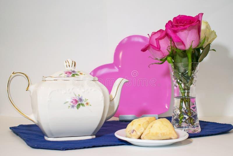 Een theepot, een roze hart, rozen en scones op plaat royalty-vrije stock foto's