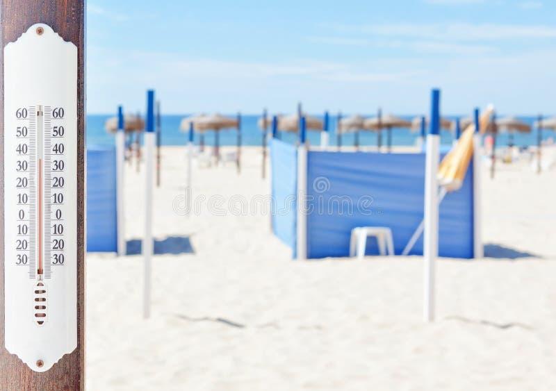 Een thermometer op het strand in de zomer. stock foto's