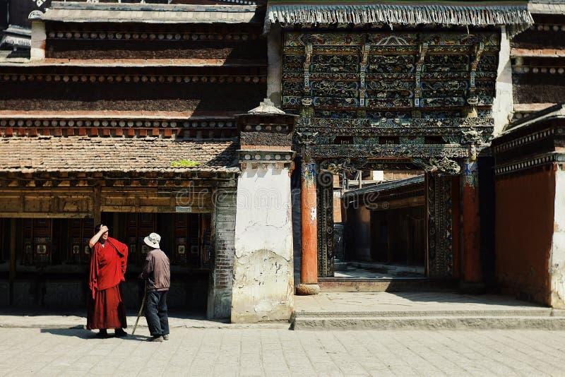 een tibetan monnik spreekt met een pelgrimsmens voor de tempel met opmerkelijke decoratie boven de poort royalty-vrije stock fotografie