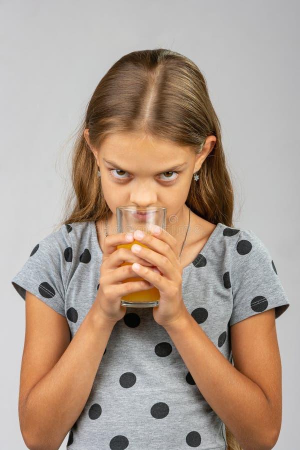 Een tien éénjarigenmeisje drinkt sap en geniet van de geur stock fotografie