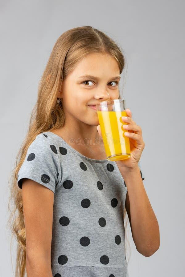 Een tien-jaar-oud meisje drinkt sap, en met een glimlach bekeek het kader stock afbeeldingen
