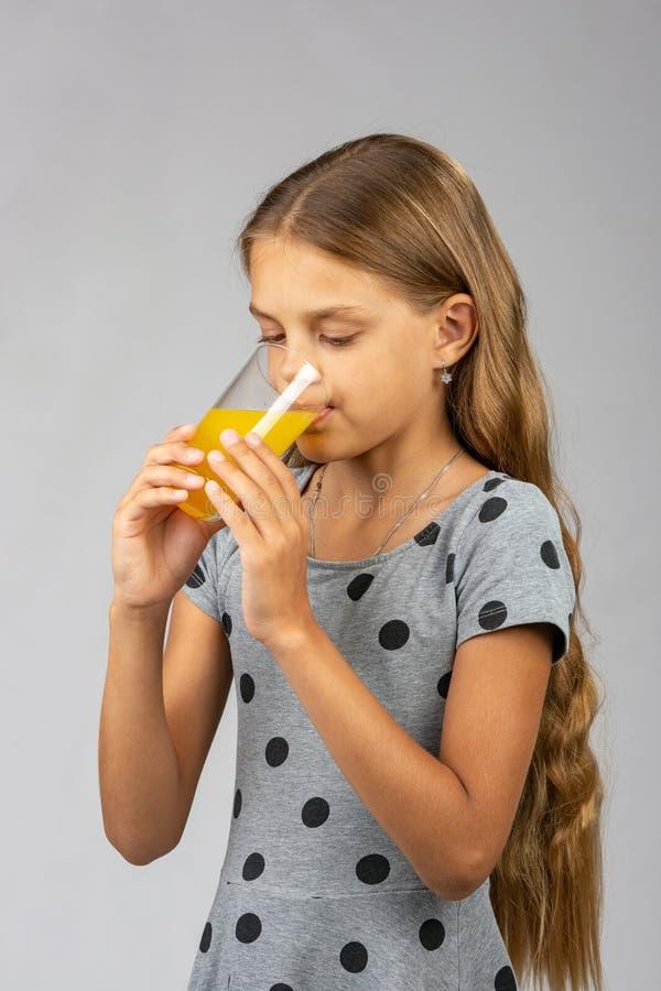 Een tien-jaar-oud meisje drinkt sap, helft-opgeruimde mening royalty-vrije stock foto's