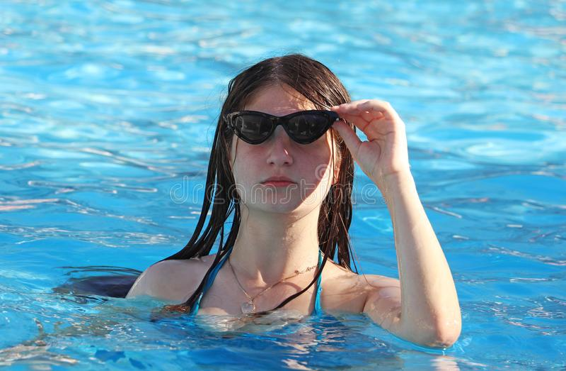 Een tiener besteedt in de pool stock afbeelding