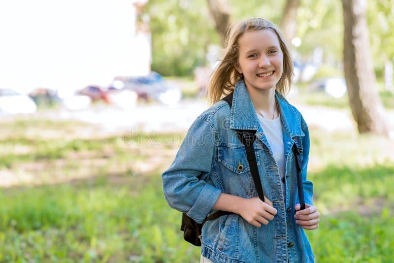 Een tiener in de zomer in park Het glimlachen gelukkig na school In aard achter de rugzak Vrije ruimte voor tekst stock fotografie
