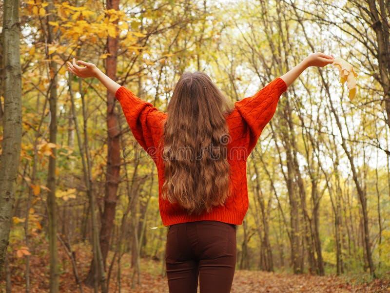 Een tiener die haar handen met vreugde opheffen Een meisje die oranje sweater en bruine jeans dragen stock foto