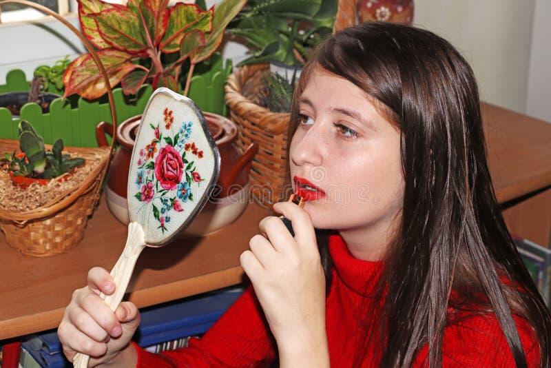 Een tiener die lippen met lippenstift retoucheren stock fotografie