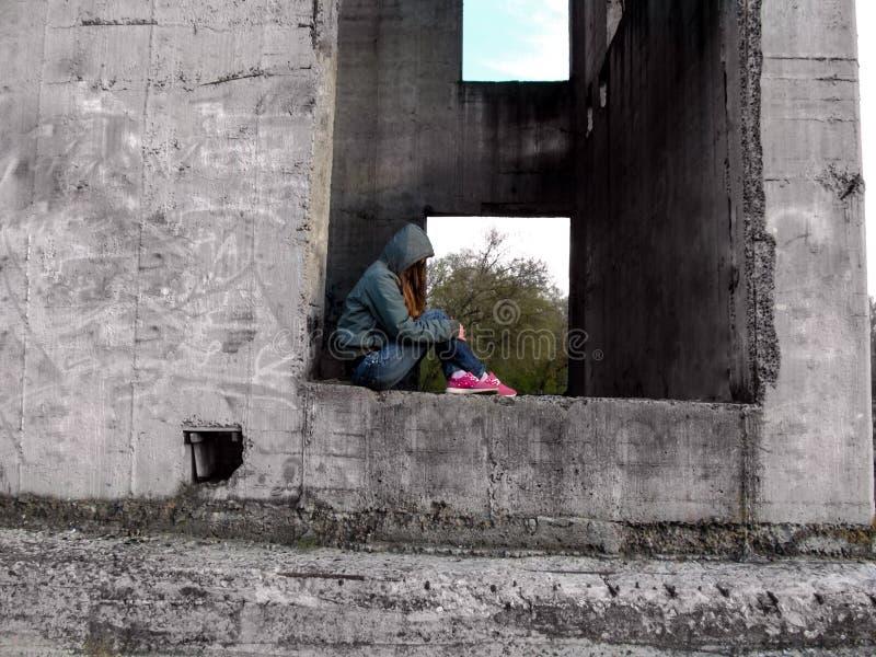 Een tiener in een kap zonder een gezicht zit in een rechthoekig gat van een concrete muur stock foto