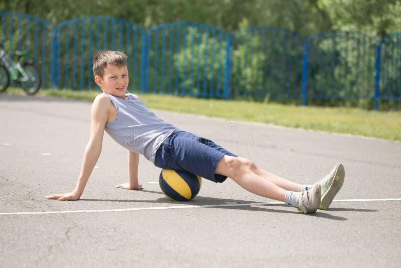 Een tiener in een T-shirt zit op bal het rusten royalty-vrije stock afbeelding
