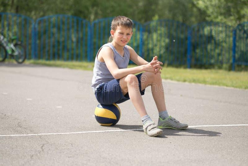 Een tiener in een T-shirt zit op bal het rusten stock fotografie