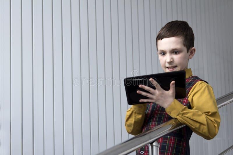 Een tiener in een geruit jasje en een geel overhemd bekijkt irritably de tablet terwijl het spelen of het werken stock afbeelding