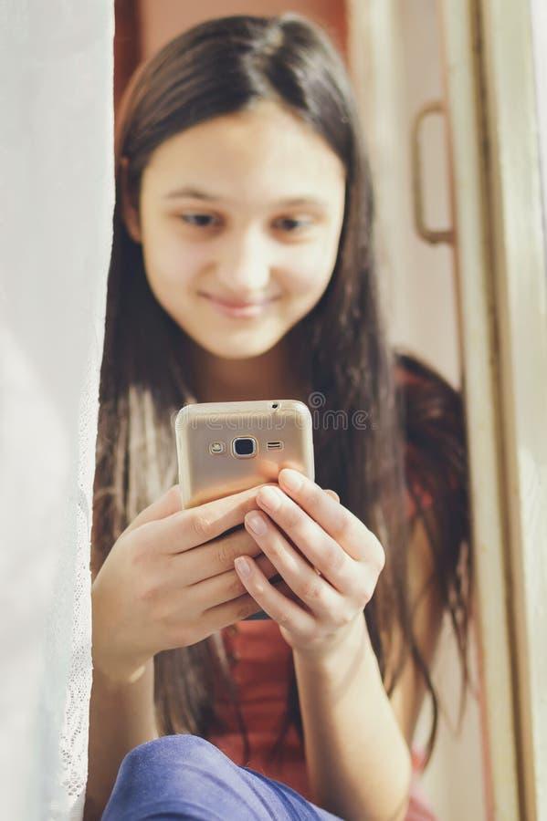Een tiener houdt een mobiele telefoon close-up, zachte nadruk stock afbeeldingen
