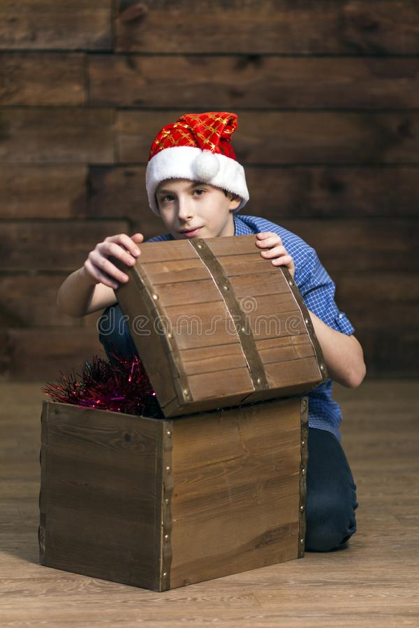 Een tiener in jeans, een geruit overhemd opent een borst met Kerstmisdecoratie op een houten achtergrond Verticale foto royalty-vrije stock foto's