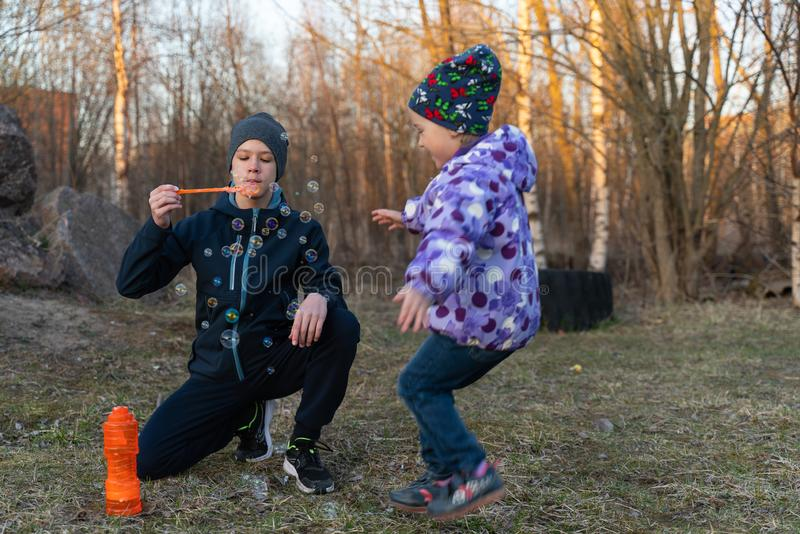 Een tiener in een matroos en een grijze hoed en een meisje die borrelen in openlucht blazen Kinderen` s portret stock foto's