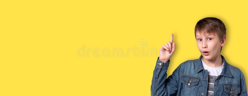 Een tiener op een gele achtergrond met een opgeheven hand Heldere emotie Oplossing voor het probleem royalty-vrije stock foto
