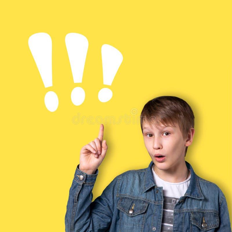 Een tiener op een gele achtergrond met een opgeheven hand Heldere emotie Oplossing voor het probleem royalty-vrije stock fotografie