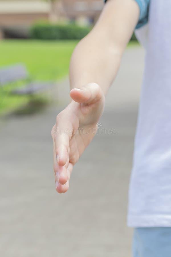 Een tiener in sportkleding breidt zijn hand voor een handdruk uit en nodigt voor uit aanstoot in het park royalty-vrije stock fotografie