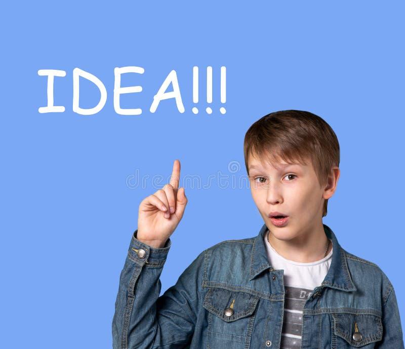 Een tiener van Europese verschijning op een blauwe achtergrond met een opgeheven hand Heldere emotie Word idee royalty-vrije stock foto's