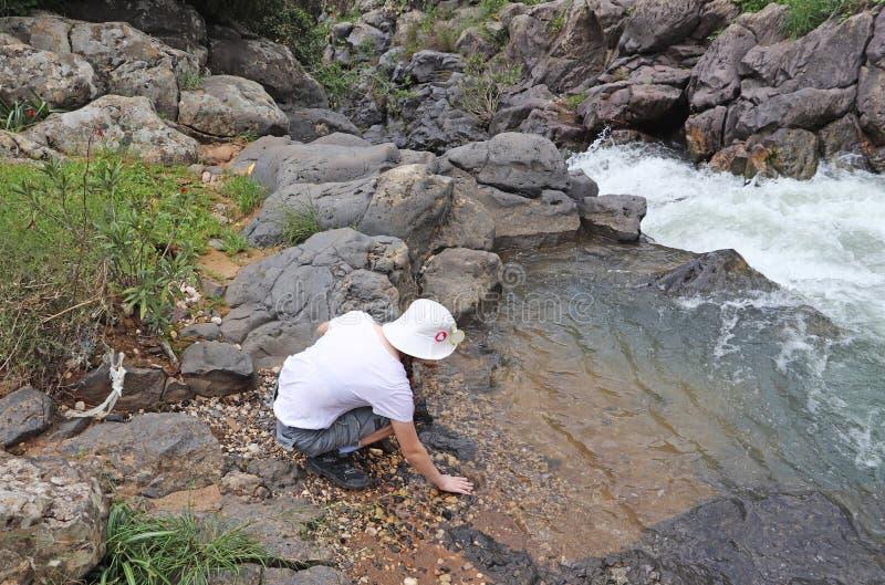 Een tiener zit op de bank van een stroom stock foto's