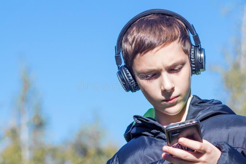 Een tiener in een zwart jasje met hoofdtelefoons bekijkt ernstig smartphone in het park op een blauwe hemelachtergrond royalty-vrije stock foto