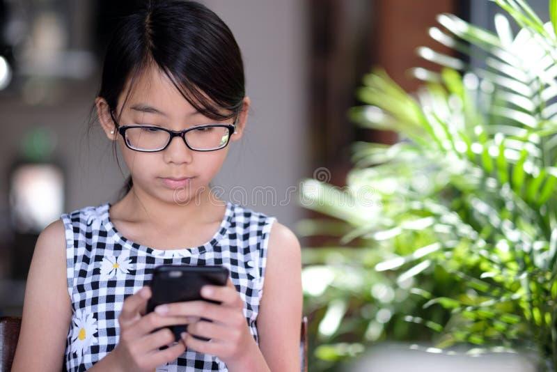 Een tienermeisje die smartphone in koffie met behulp van royalty-vrije stock foto's