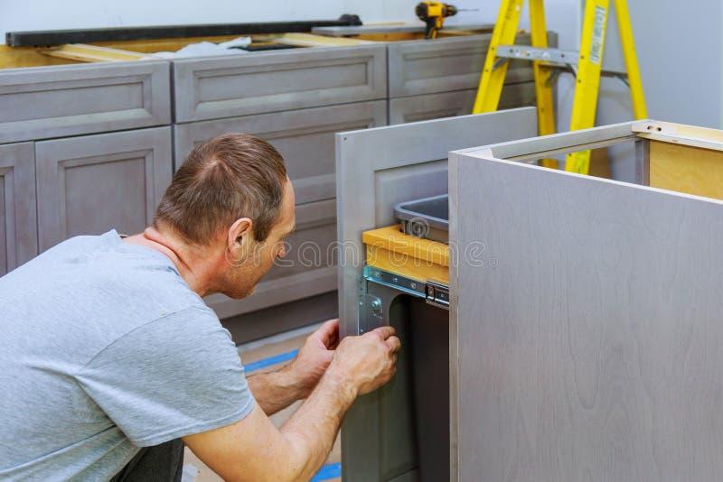 Een timmerman bouwt een bak van het ladenhuisvuil in de keuken stock foto's
