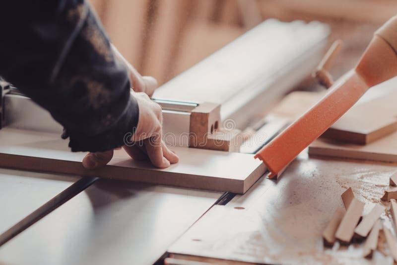 Een timmerman werkt bij de houtbewerking de werktuigmachine Timmerman die aan houtbewerkingsmachines werken in timmerwerkwinkel stock afbeelding