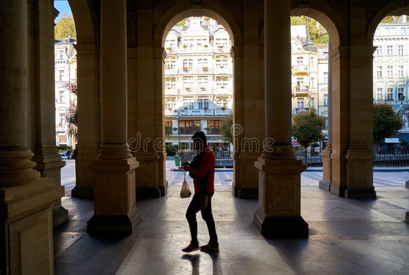 Een toerist die door de populaire Molencolonnade lopen in de Oude Stad van Karlovy varieert stock fotografie