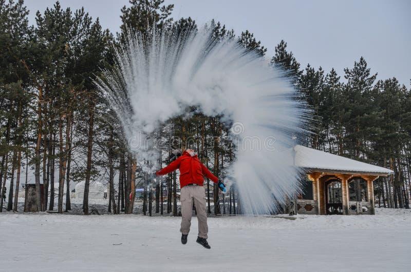 Een toerist die warm water werpen bij de winterpark royalty-vrije stock fotografie