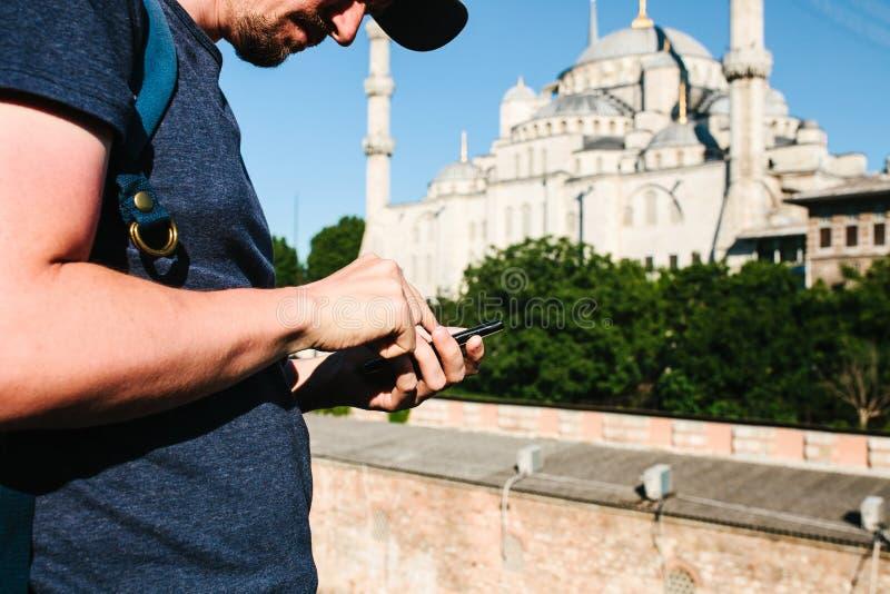 Een toerist gebruikt een mobiele telefoon Op de achtergrond is de Blauwe Moskee in Istanboel royalty-vrije stock foto