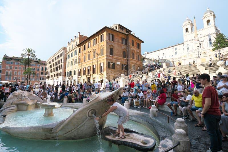Een toerist probeert om een fles met water bij fontein van de boot bij Spaans vierkant te vullen royalty-vrije stock afbeeldingen