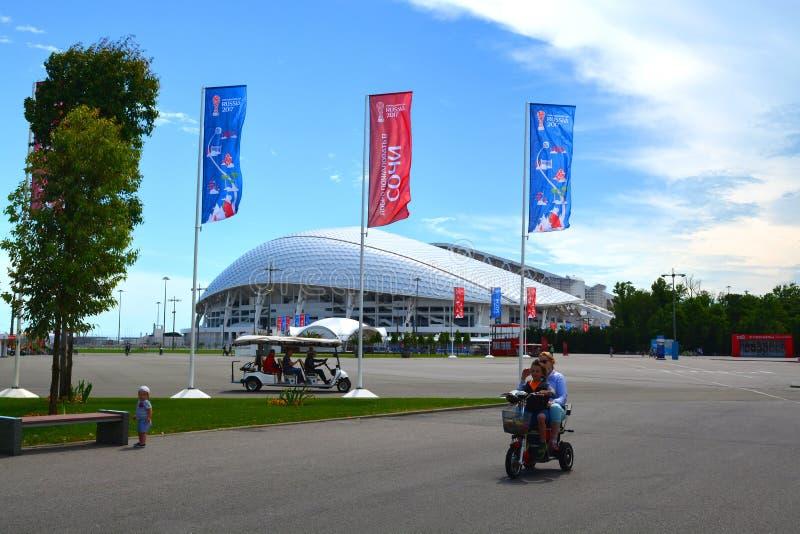 Een toeristen elektrische auto en een familie op een elektrische fiets op de achtergrond van het stadion van ` Fisht ` stock foto's