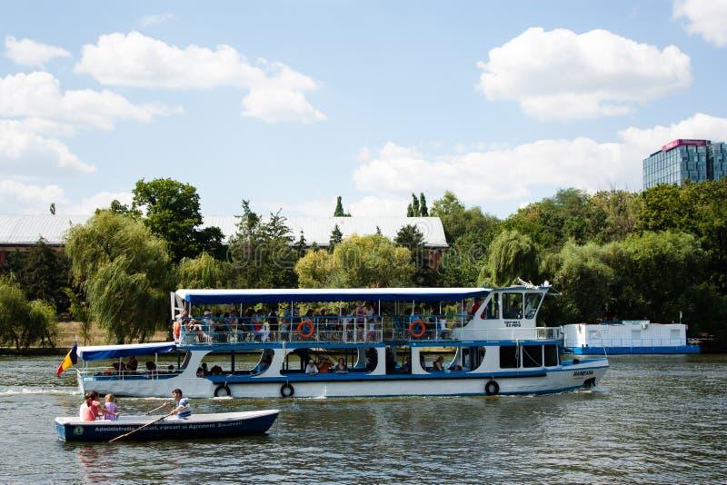 Een toeristenboot en een het roeien boot op Herastrau-meer stock foto's