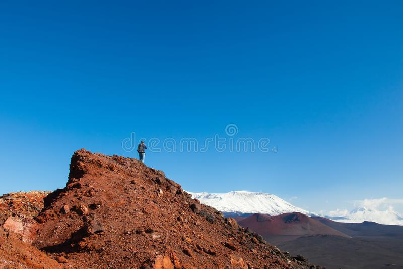 Een toeristenfotograaf bij de bovenkant van de berg neemt beelden van het landschap van vulkanen royalty-vrije stock fotografie