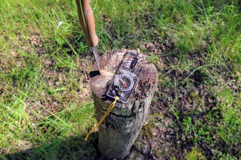 Een toeristenkompas ligt in het bos op een stomp stock afbeeldingen