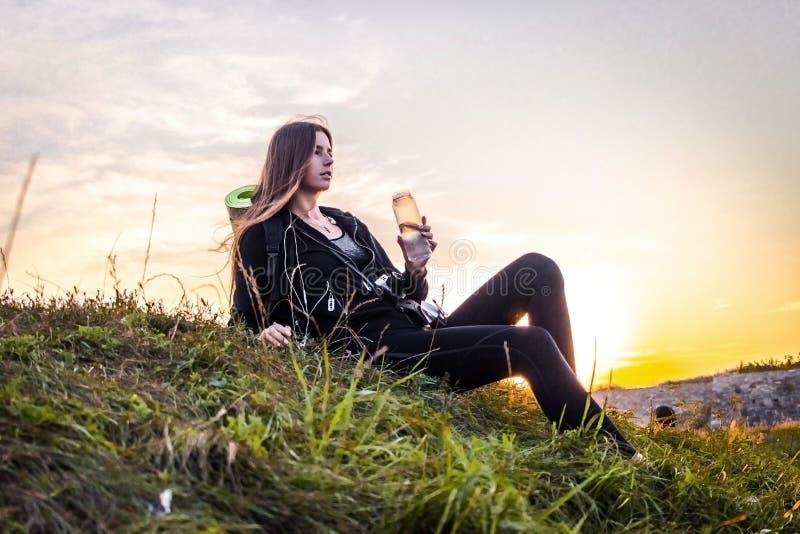 Een toeristenmeisje drinkt water in helder zonlicht royalty-vrije stock afbeelding