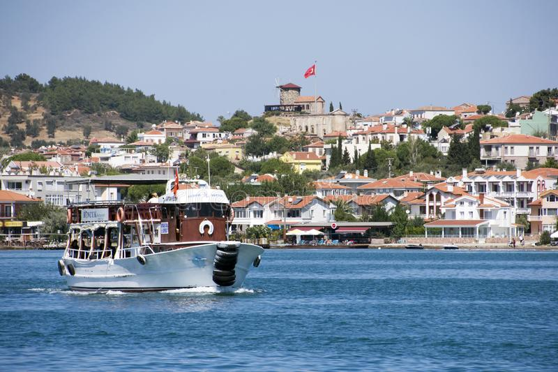 Een toeristenschip met steenwindmolen in Ayvalik, Turkije stock afbeeldingen