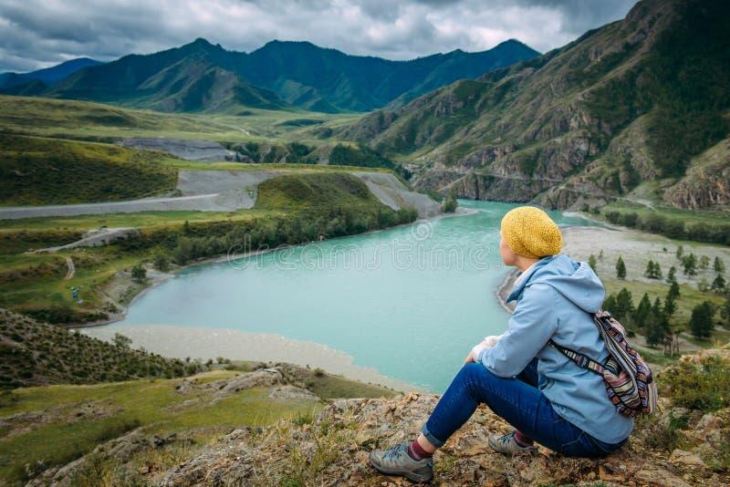 Een toeristenvrouw met een rugzak zit bovenop de berg en bekijkt de samenloop van de rivieren Chui en Katun royalty-vrije stock foto's