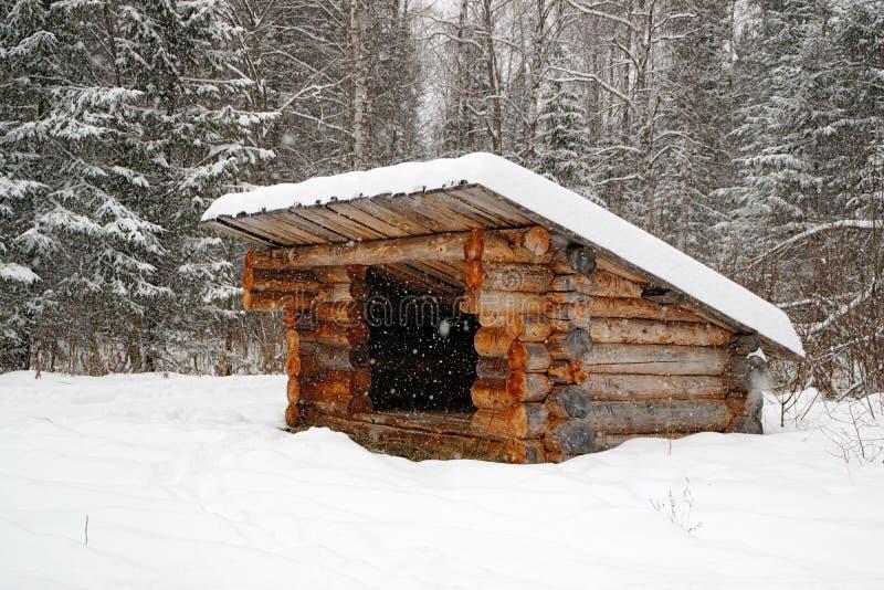 Een toevluchtsoord voor aanhangers in het bos in de winter, een structuur van logboeken met een dak royalty-vrije stock afbeeldingen