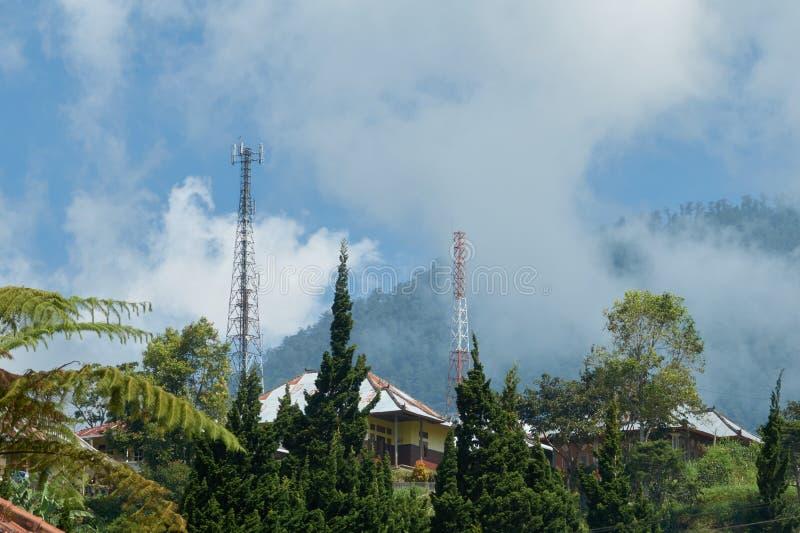 Een toren van cellulaire mededeling over een heuvel van een berg in wolken stock foto's