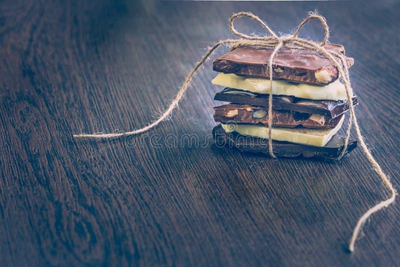 Een toren van chocoladerepen als een aanwezige die chocolade worden verpakt Diverse chocoladestukken over donkere houten achtergr royalty-vrije stock foto