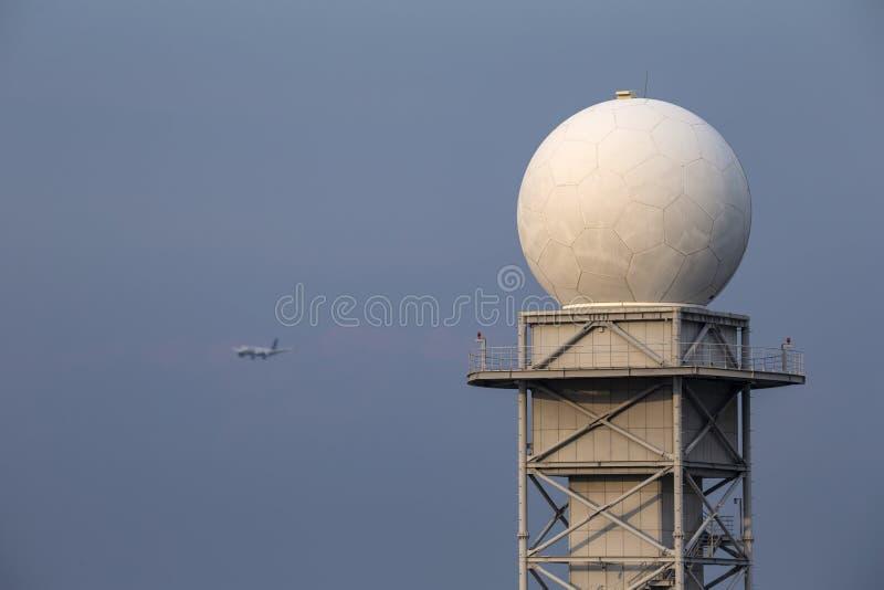 Een toren van de weerradar met blauwe hemelachtergrond en blured vliegtuig stock foto's